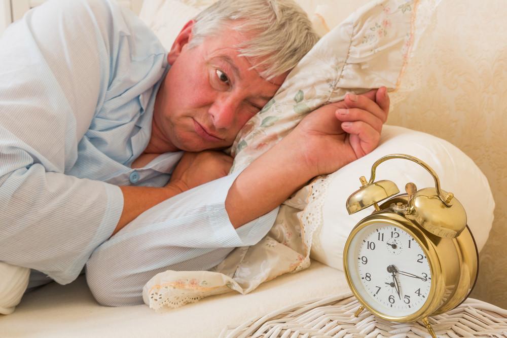 mann schlaeft im bett vor wecker