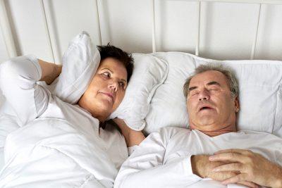 Eine Frau hält sich im Bett mit einem Kissen die Ohren zu, weil ihr Mann, der neben ihr liegt, laut schnarcht
