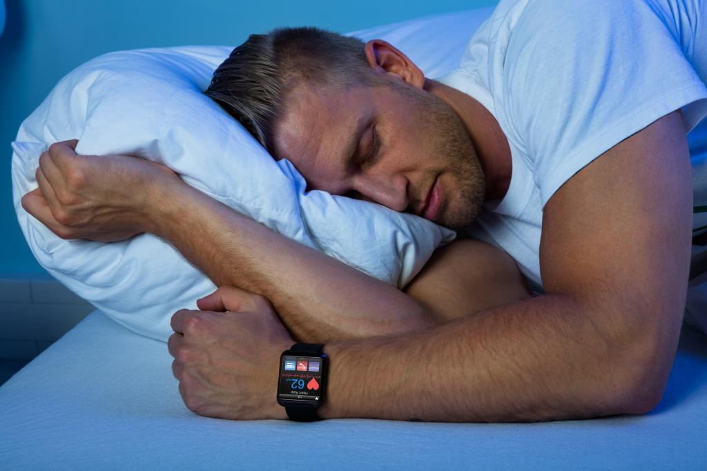 Ein Mann trägt zur Schlafanalyse beim Schlafen eine Apple Watch