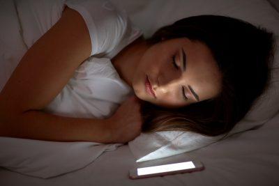 Ein Smartphone überwacht den Schlaf einer Frau